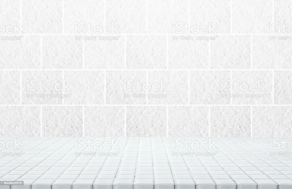 White ceramic mosaic table top and background of grey granite stone tile wall - can used for display or montage your products. stock photo
