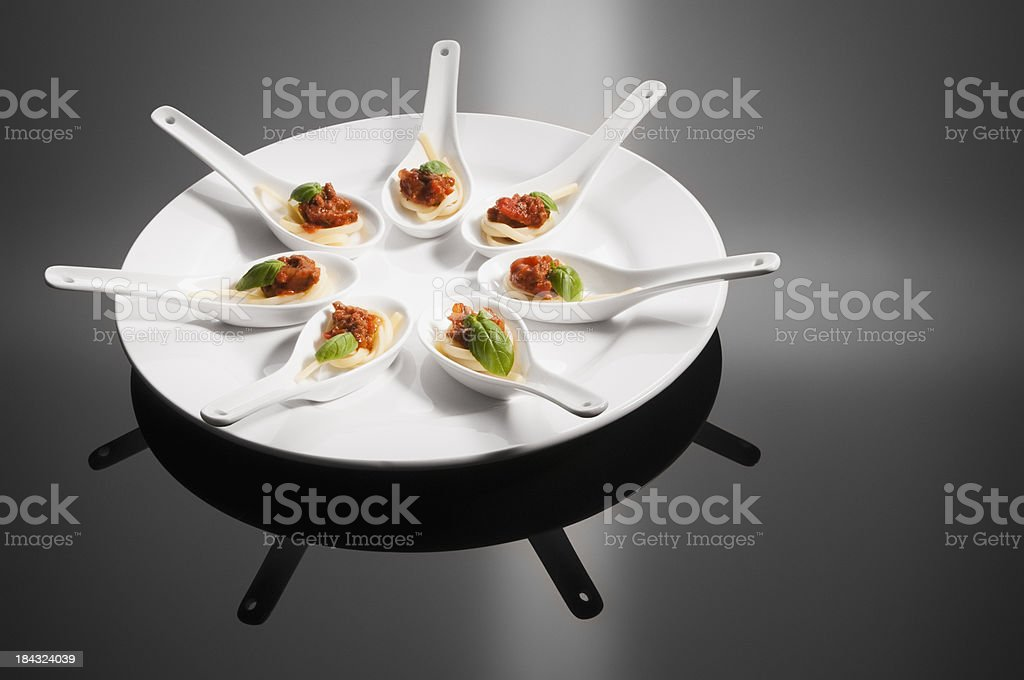 White ceramic spoons holding canapés on round plate royalty-free stock photo