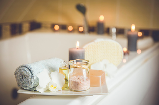 istock White ceramic tray with home spa supplies in home bathroom for relaxing rituals. Candlelight, salt soap bar, bath salt in jar, massage, bath oil in bottle, blue rolled towel, natural sponge. 1136976095