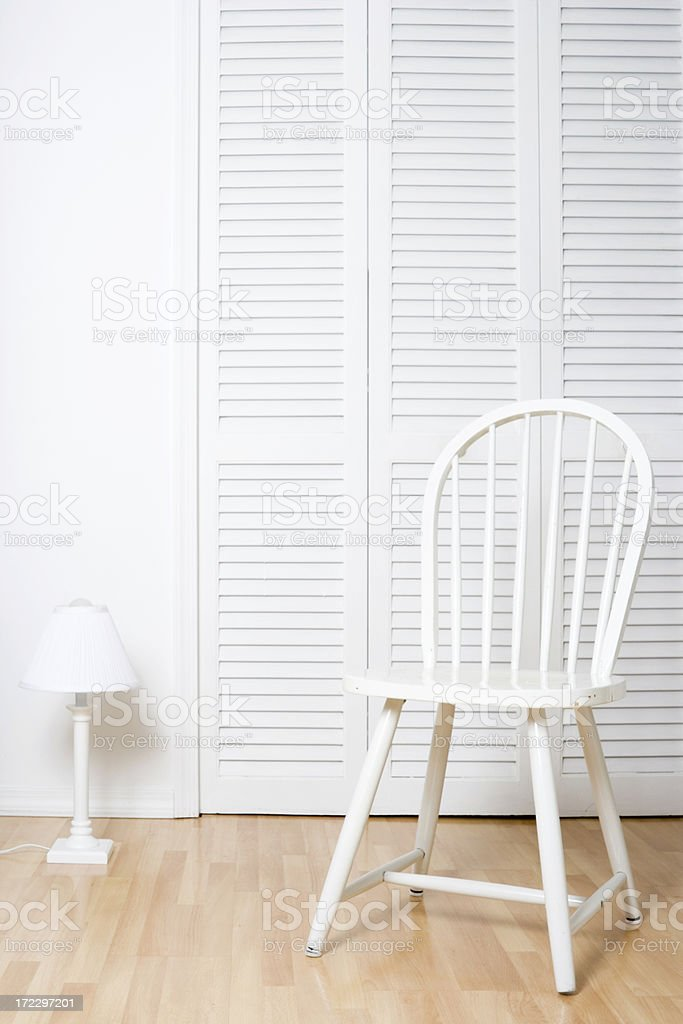 White chair and louvered doors stock photo