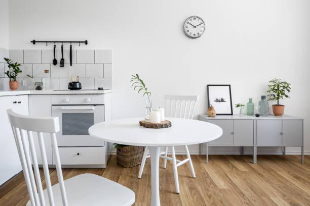 weiße stühle und ein runder tisch - sideboard skandinavisch stock-fotos und bilder