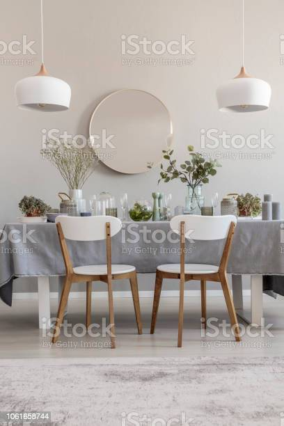 White Chairs At Table In Elegant Dining Room Interior With Round Mirror And Lamps Real Photo Stock Photo Download Image Now Istock