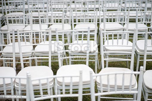 White chairs on top of grass field for wedding