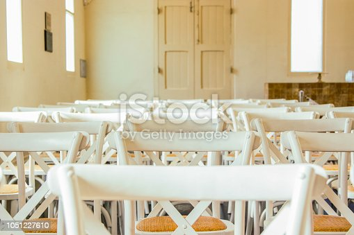 Partial view of white French cross-back timber chairs arranged for an event inside an old building. Seating is set up for Wedding Ceremony. No people.