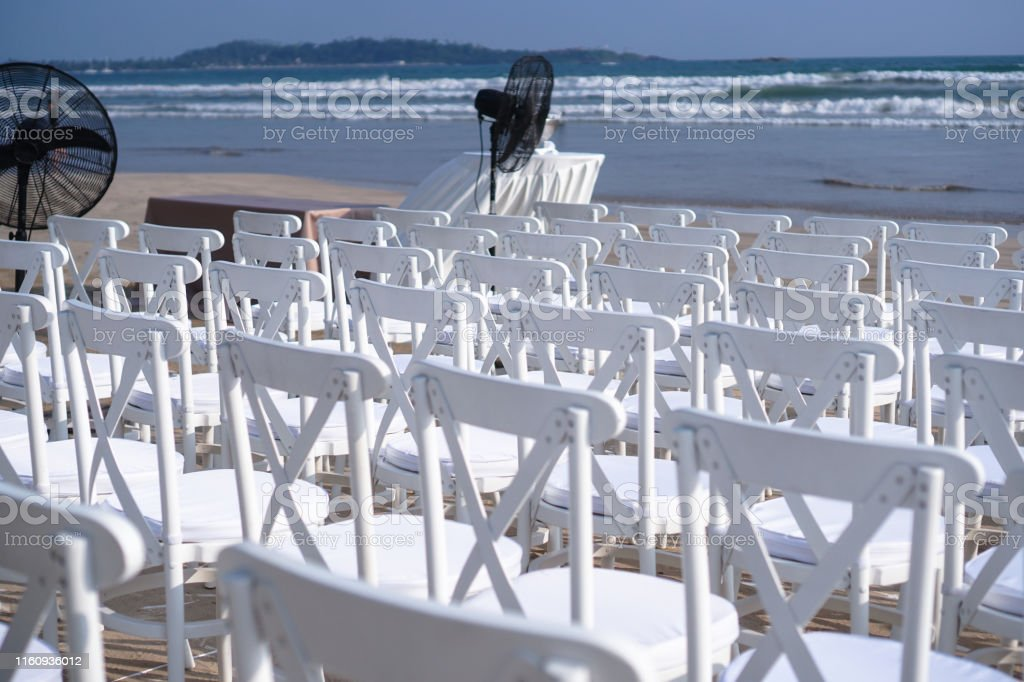 White chairs stand on the beach in rows. Outdoor conference....