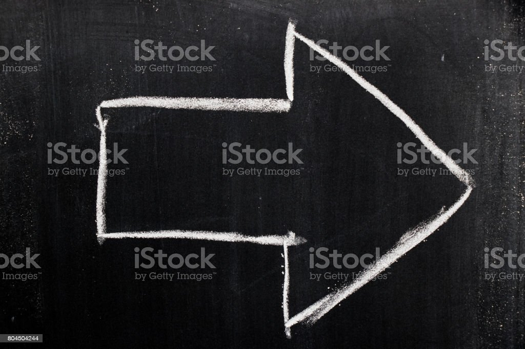 White chalk drawing as arrow shape on black board background stock photo