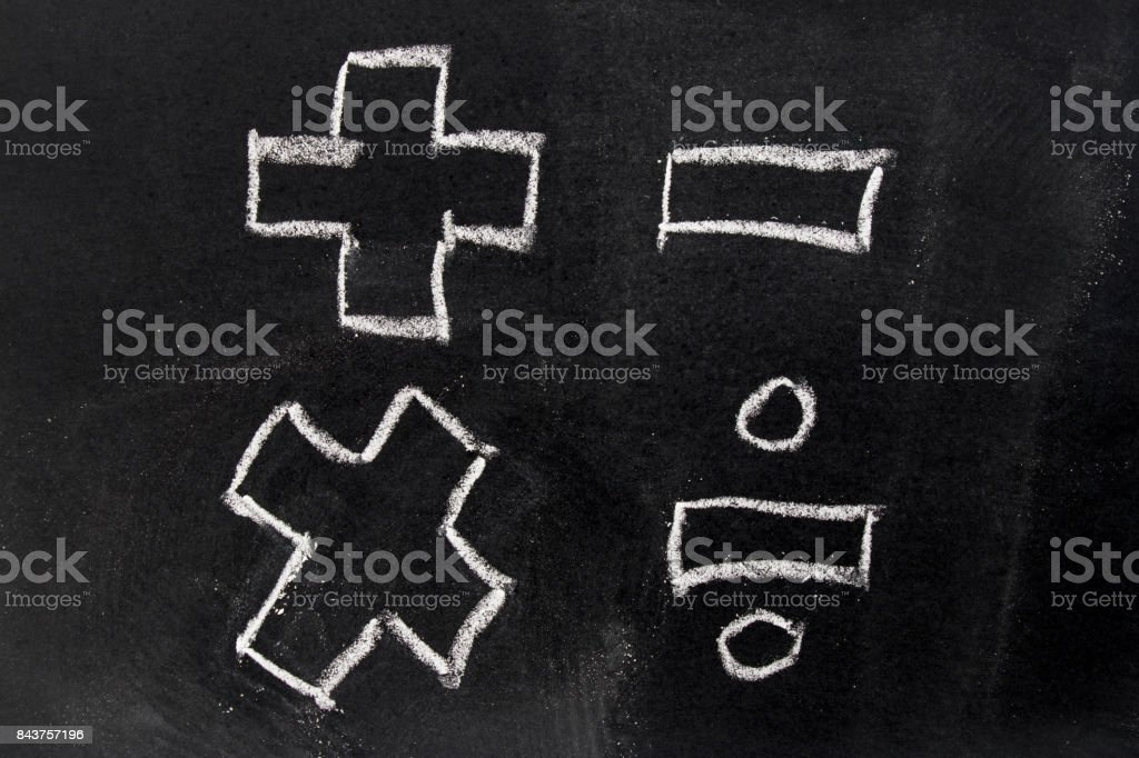 White chalk drawing in basic mathematics symbol (plus minus multiply divide) on black board background stock photo