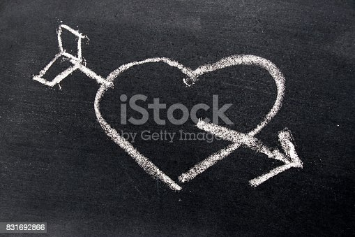 istock White chalk drawing in heart with arrow shape on black board background use for decoration in valentine, love, couple or engagement concept 831692866