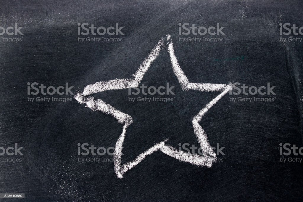White chalk hand drawing as star shape on black board background stock photo