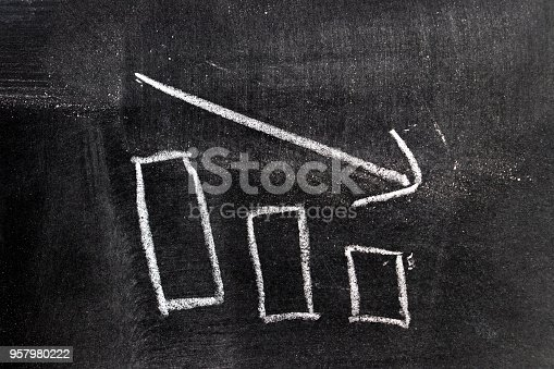 istock White chalk hand drawing in bar chart with downtrend arrow shape on blackboard background 957980222