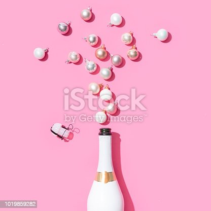 istock White champagne bottle with Christmas baubles decoration on pink background. 1019859282