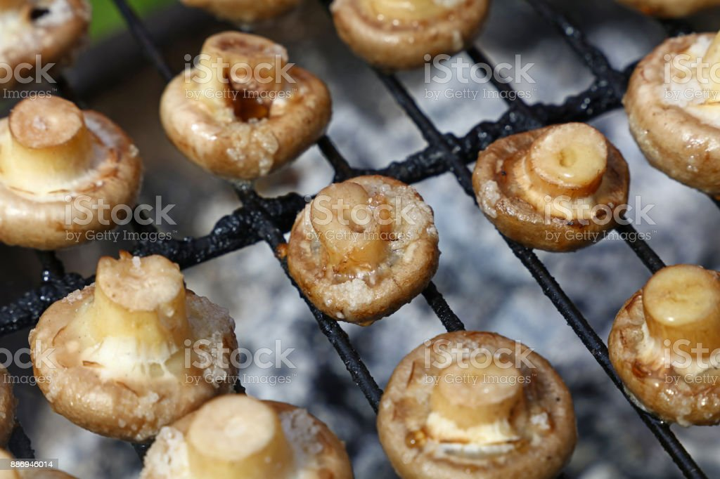 White champignons mushrooms on grill stock photo