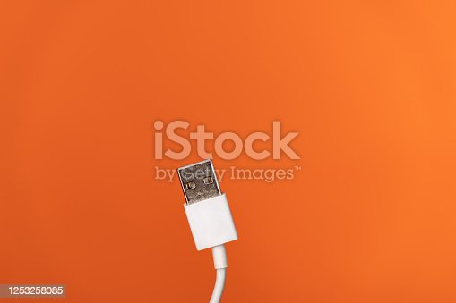 White charging cable for  smartphone or  digital tablet on orange background.  The scene is situated in controlled studio environment in front of orange background. Photo is taken with SONY AIII camera