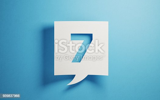 White chat bubble on  blue background. Number seven writes on chat bubble. Horizontal composition with copy space.