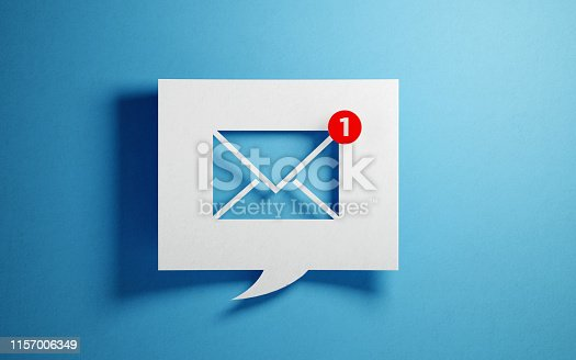 White chat bubble with email symbol on blue background. Horizontal composition with copy space.