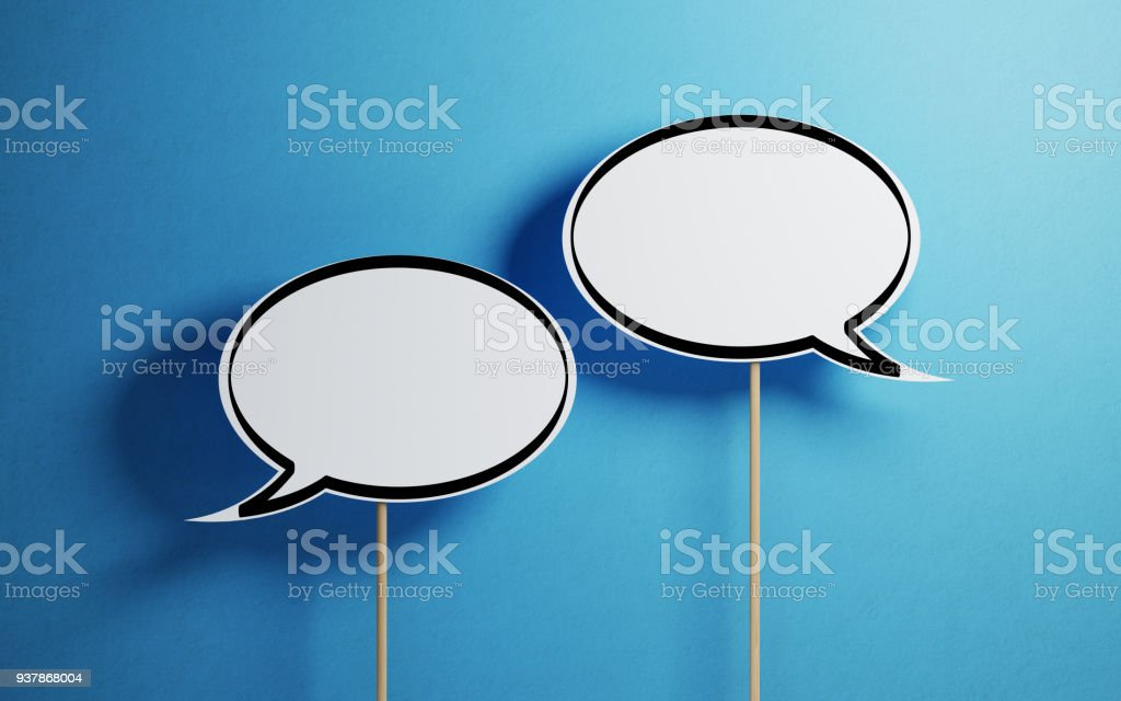 White Chat Bubbles With Wooden Sticks On Blue Background White chat bubbles with wooden stickson  blue background. Horizontal composition with copy space. Discussion Stock Photo
