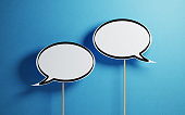 White chat bubbles with wooden stickson  blue background. Horizontal composition with copy space.