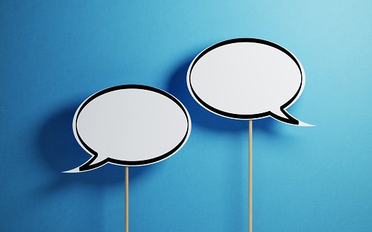 White Chat Bubbles With Wooden Sticks On Blue Background Stock Photo - Download Image Now