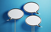 White Chat Bubbles With Wooden Sticks On Blue Background