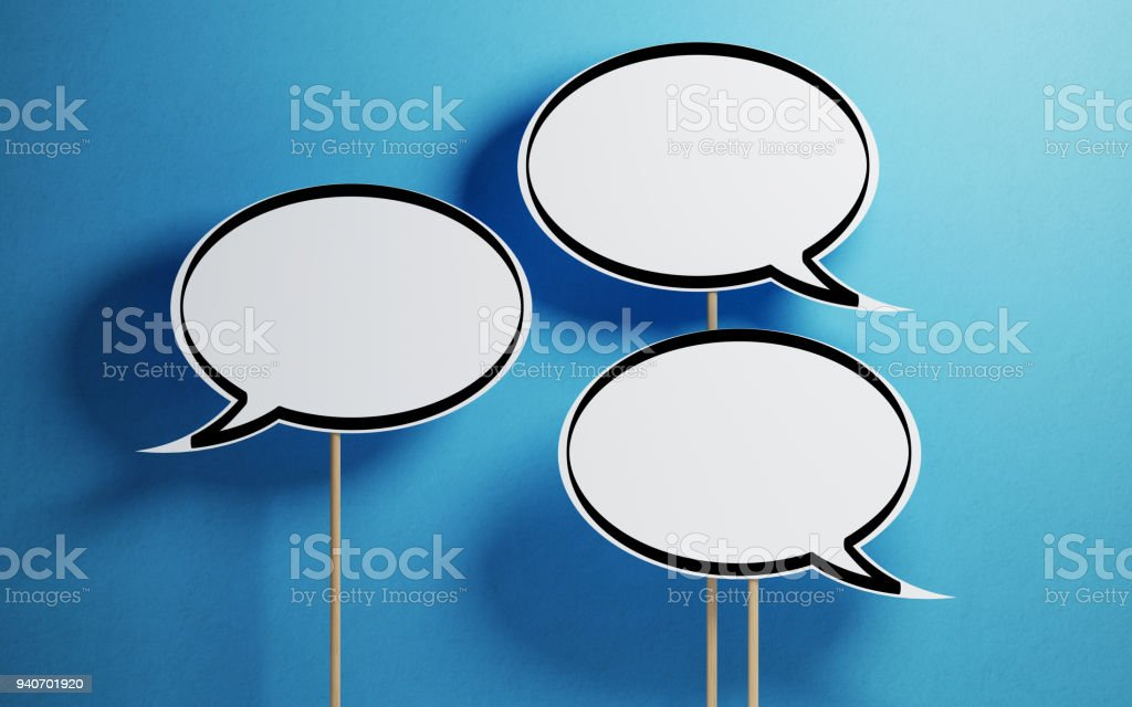 White Chat Bubbles With Wooden Sticks On Blue Background stock photo