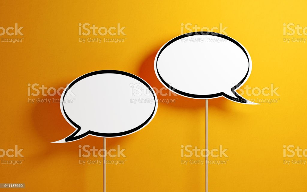 White Chat Bubbles With Wooden Sticks On Yellow Background stock photo