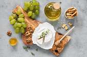 istock White cheese plate with crackers, honey, grapes 1127282593