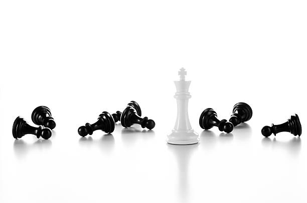 White Chess King among lying black Pawns, isolated on white stock photo