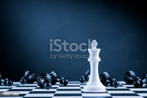 Leader and competition. White Chess King among lying down black pawns on chessboard, dark blue background.