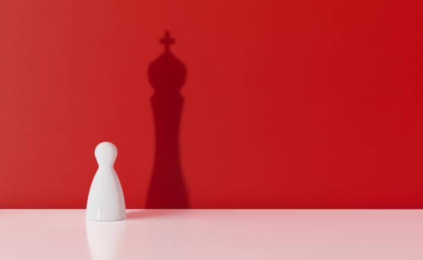 Peão de xadrez branco, lançando a sombra de um rei sobre Red Background - foto de acervo