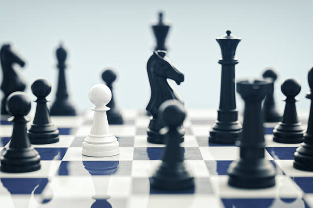 White Chess Pawn Surrounded By Black Chess Pieces White chess pawn surrounded by black chess pieces on a chess board. surrounding stock pictures, royalty-free photos & images