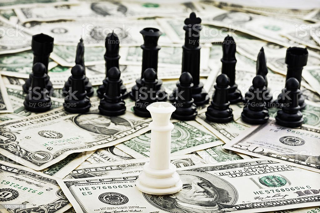 White chess queen confronts black pieces on pile of dollars royalty-free stock photo