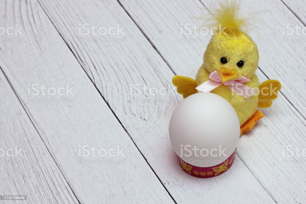White chicken egg is located next to funny yellow fluffy toy chicken...
