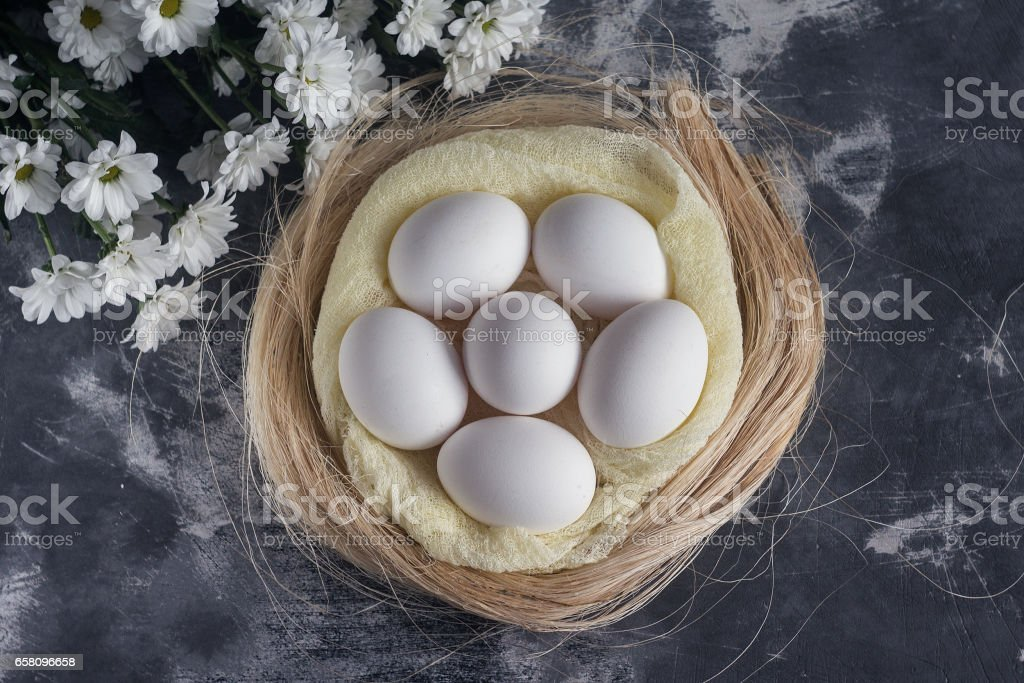 White chicken eggs in easter nest on gray background. Top view royalty-free stock photo