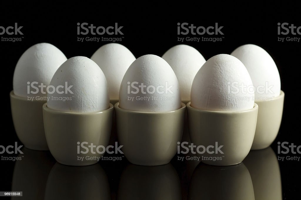 white chicken eggs in egg-cups on black reflecting background royalty-free stock photo