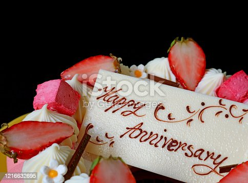 1129427811 istock photo White chocolate anniversary edible greeting card on the top of strawberry jelly vanilla mousse cake 1216632695