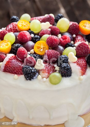 472311978 istock photo White chocolate cake decorated with fresh berries and fruits 472311974