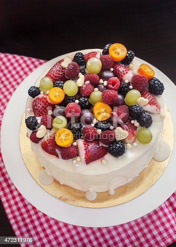 istock White chocolate cake decorated with fresh berries and fruits 472311976