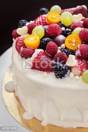 istock White chocolate cake decorated with fresh berries and fruits 472311978