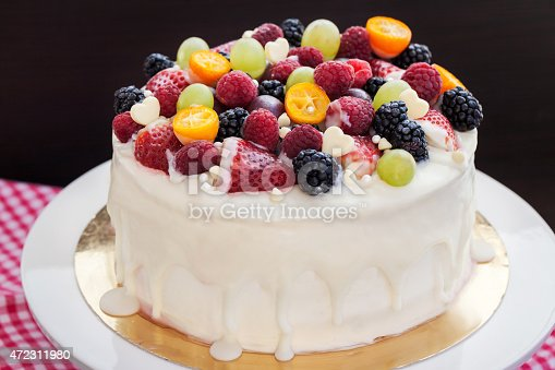 istock White chocolate cake decorated with fresh berries and fruits 472311980