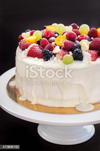 istock White chocolate cake decorated with fresh berries and fruits 472805152