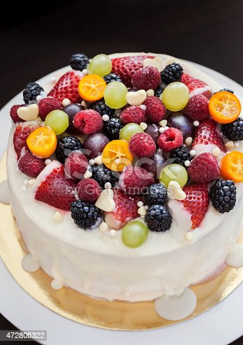 istock White chocolate cake decorated with fresh berries and fruits 472805322