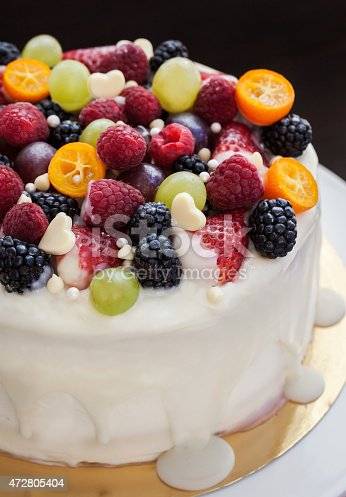 istock White chocolate cake decorated with fresh berries and fruits 472805404