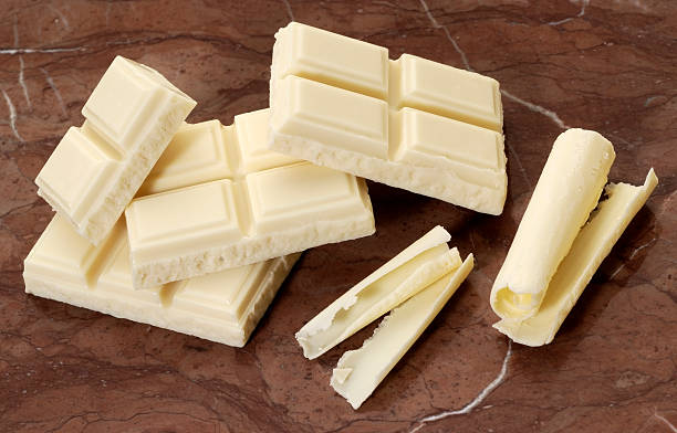 White chocolate chunks and shavings on brown marble stock photo