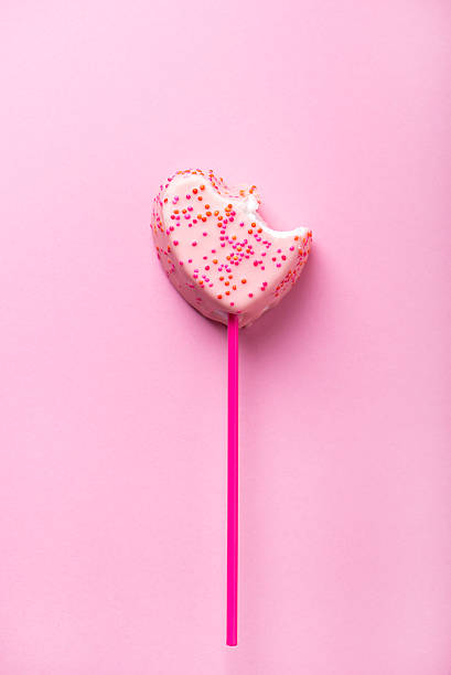 white chocolate covered marshmallow in heart shape with a bite stock photo