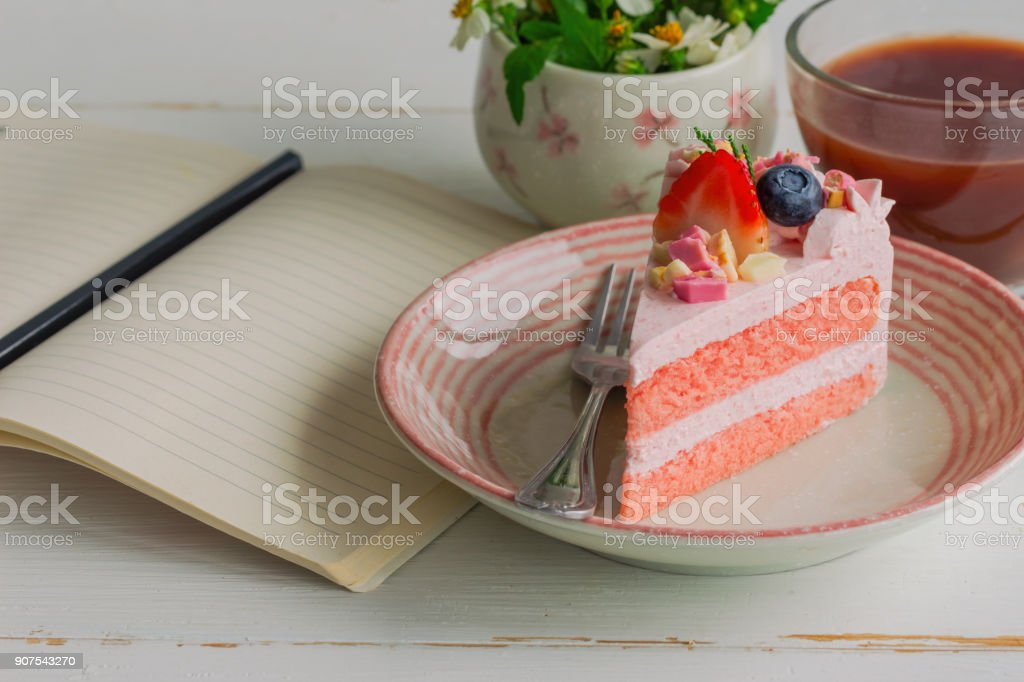 White chocolate strawberry yogurt cake decorated with fresh fruits and chocolate chunk on wood table near notebook. Delicious and sweet pink cake for Valentines or birthday. Homemade bakery concept. stock photo