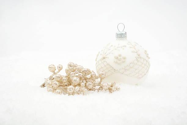 weiße weihnachtskugel mit gold elemente auf schnee - schnelles weihnachtsessen stock-fotos und bilder