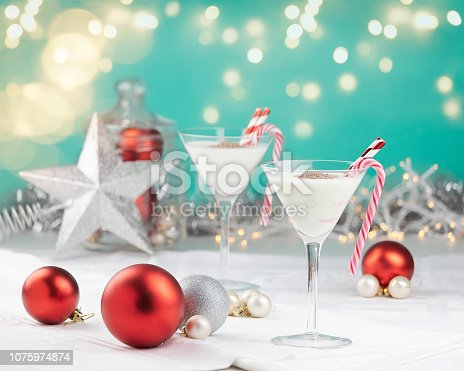 White Christmas cocktails with candy canes and straws in a red and teal setting with out of focus lights, christmas decoration