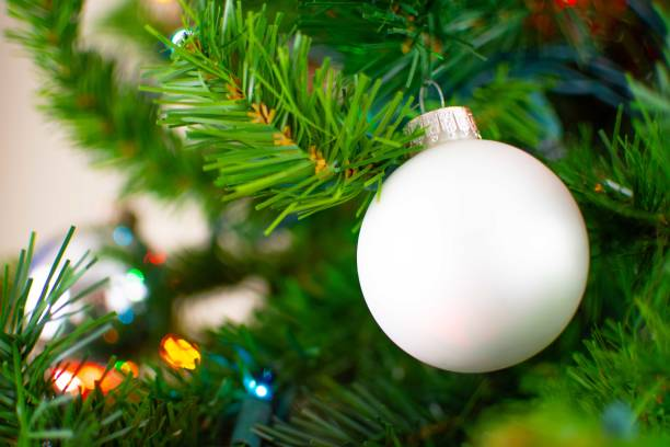 A white Christmas decoration hangs on a green tree stock photo