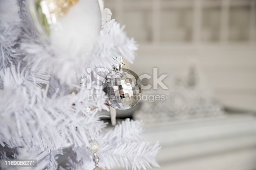 istock White Christmas decoration with balls on fir branches with blurred background.Silver christmas balls . Merry christmas and happy new year. Holiday postcard. Copy space 1169086271
