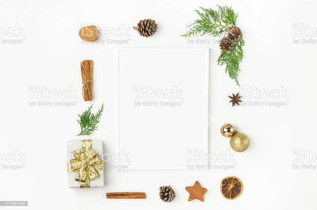 White Christmas frame mockup. Gift box in wrapped silver paper with golden ribbon pine cones juniper nuts cinnamon. New Year presents holiday preparations DIY. Minimalist poster banner stock photo
